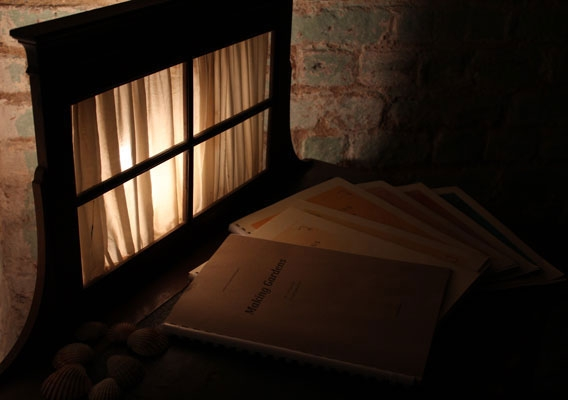 A series of artist publications on a desk - back lit